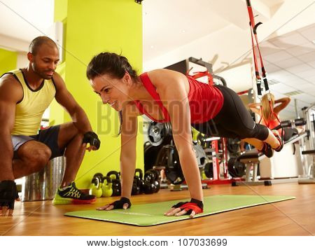 Sporty woman doing TRX suspension training with personal trainer in gym.