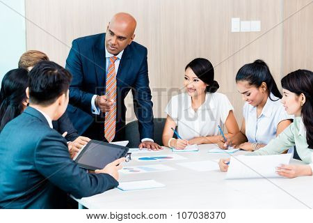 Diversity team in business development meeting with charts, Indian CEO and Caucasian executive crunching numbers, charts and figures on the desk