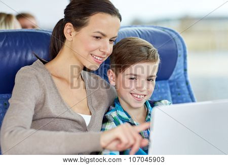 travel, tourism, family, technology and people concept - happy mother and son with tablet pc computer sitting in travel bus or train
