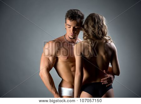 Muscular hunk embracing topless model by waist