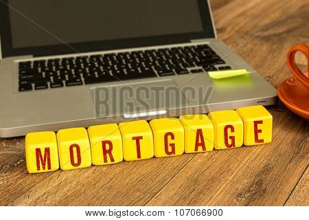 Mortgage written on a wooden cube in front of a laptop