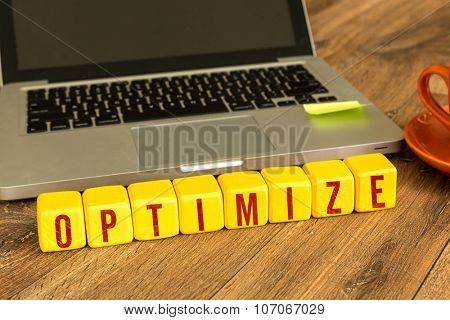 Optimize written on a wooden cube in front of a laptop poster