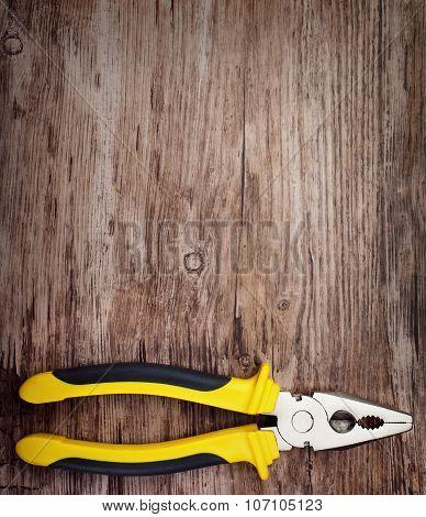 handtools  pliers on wooden doard