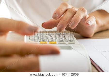 Front view of female banker calculating expenses and income using adding machine while checking a printout receipt. poster