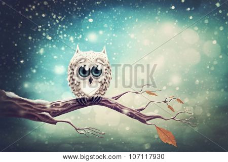 Little snow owl sitting on the branch