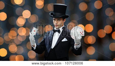 magic, performance, gambling, casino, people and show concept - magician in top hat showing trick with playing cards over nigh lights background