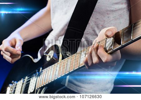 music, people, musical instruments and entertainment concept - close up female musician hands playing electric guitar with mediator poster