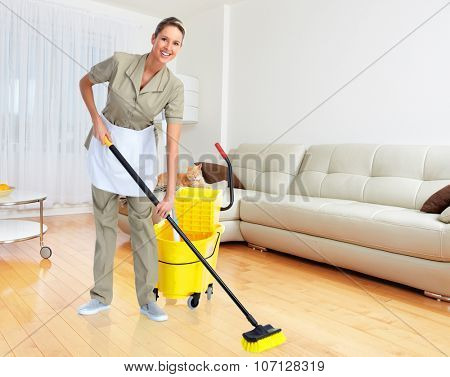 Smiling housewife cleaner with broom in modern apartment background