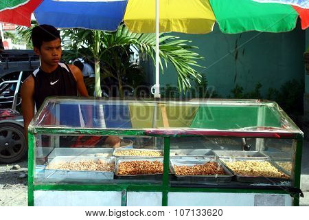 market vendor sells different kinds of roasted peanuts