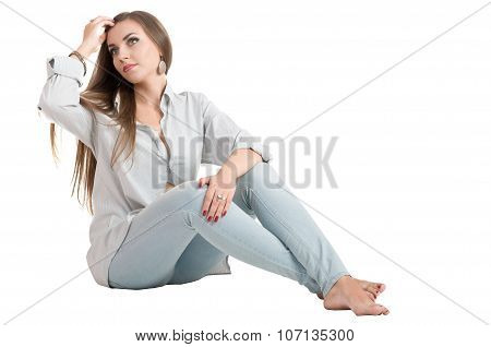 Beautiful Young Girl With Long Brown Hair Sitting On The Floor In Jeans