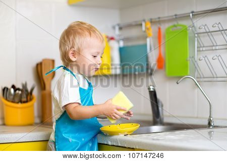 Boy cleaning the kitchen after making dinner