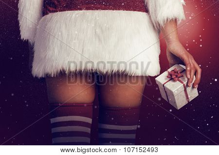 Pretty girl in santa outfit holding gift against snow poster