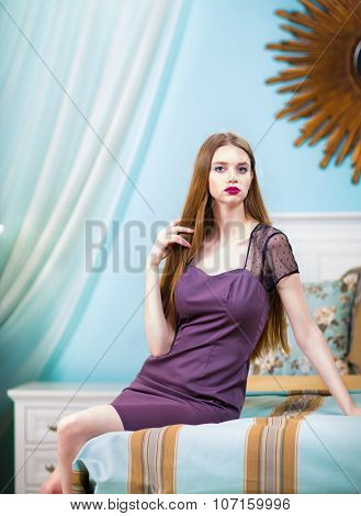 Beautiful Woman In Purple Dress In Luxury Bedroom Interior.