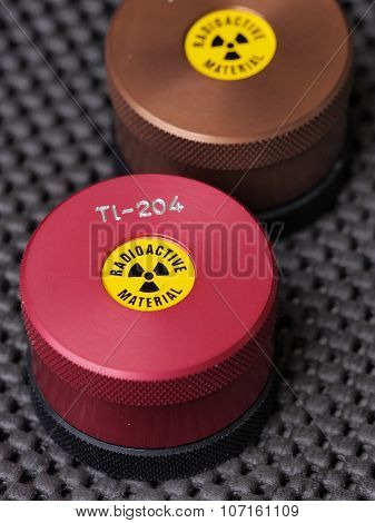 Specialist containers with warning sticker and engraving containing radioactive isotopes