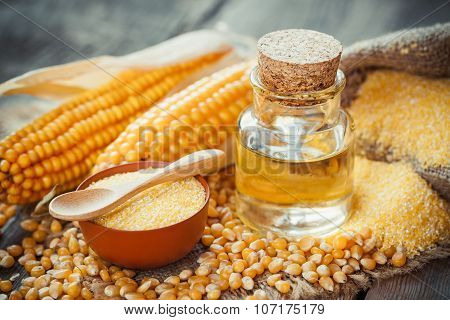 Corn Essential Oil Bottle, Corn Groats, Dry Seeds And Corncobs On Wooden Rustic Table.