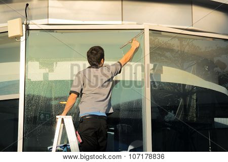 Man Housekeeper window cleaner working outside building poster
