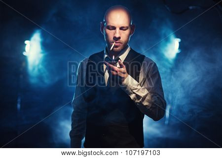 Man With A Cigarette And Lighter Against A Dark Background