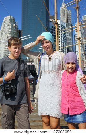 Mother with son and daughter standing on the pier near the sailing ship in New York