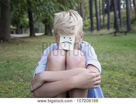 Crying Boy Sits On Green Grass In Forest. Concept Of Sad Thoughts And Negative Emotions.