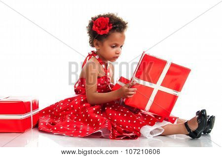 Curly Girl In A Red Polka-dot Dress Parses New Year Holiday Gifts