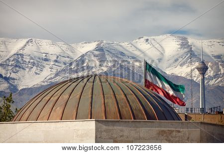 Iran Flag And Milad Tower In Front Of Snow Covered Alborz Mountains