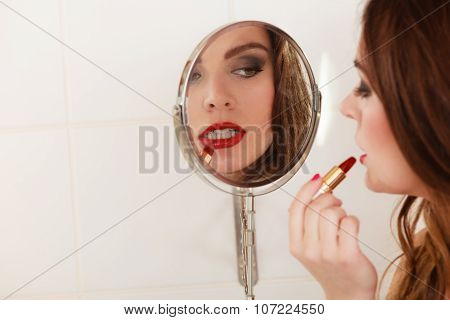 Young girl making makeup in bathroom. Woman take care about look. Looking into a mirror. poster
