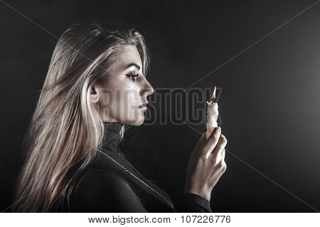 Young Woman Holding A Candle In A Smoke