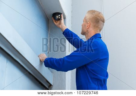 Technician Installing Camera In Corner