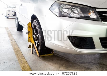 Front car wheel clamped for illegal parking a violation at commercial car parks poster