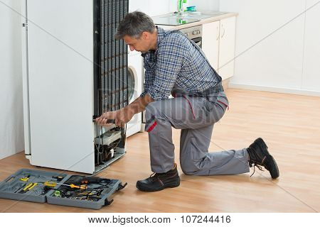 Handyman Repairing Refrigerator At Home