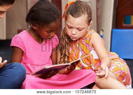 Two girls watching together a picture book in kindergarten