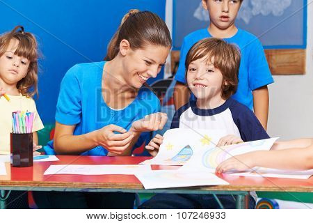 Happy children drawing with smiling nursery teacher in kindergarten