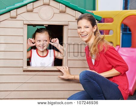 Happy educator playing with girl in playhouse in kindergarten