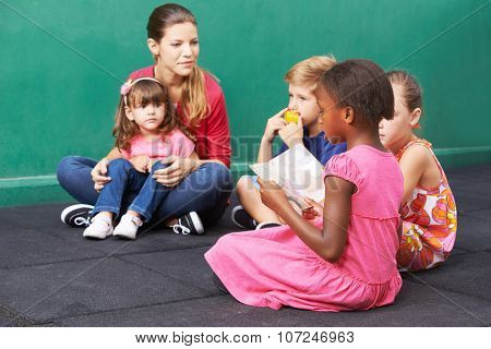African girl reading aloud for group of children in a kindergarten
