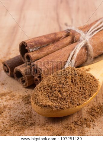 Powdery Cinnamon And Sticks On Wooden Table, Seasoning For Cooking