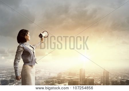 Young businesswoman in suit proclaiming something in megaphone