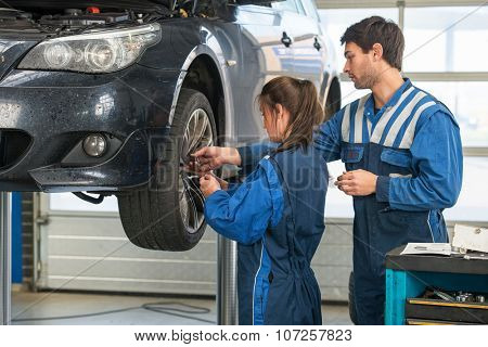 Mechanic teaching an intern the best practice. Learning on the job during a practical internship in a garage