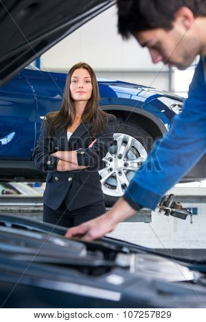 A business woman waits confidently, whilst a service mechanic is looking at the engine under the hood, examining her car in a garage