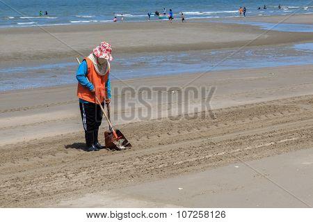CHONBURI, THAILAND - JUNE 29 2014 : Woman worker cleans on Bangsean beach at Chonburi province on June 29, 2014 in Chonburi,Thailand