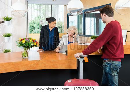 Man with luggage looking at female receptionist using technologies at counter in hotel