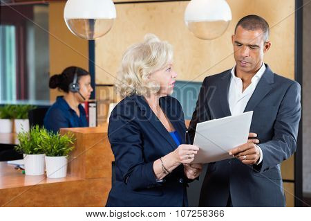 Businesspeople discussing on paperwork while receptionist working at counter in office poster