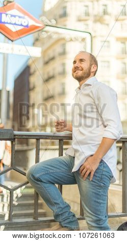 smiling man leaning on the metro entrance rail in Madrid