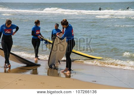 Young Surfer Friends In Wetsuits Walking Along The Shore With Their Surfing Boards. Zandvoort, The N