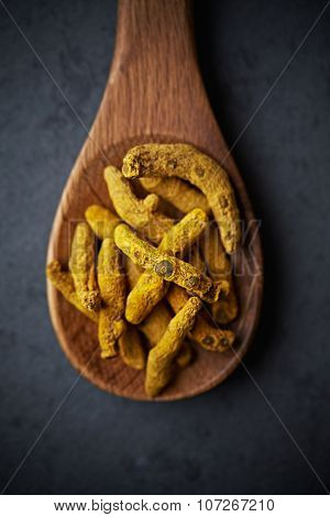 Turmeric rhizome  on a wooden spoon (close up)