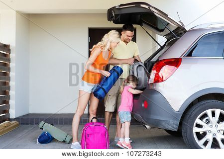 transport, leisure, travel, road trip and people concept - happy family packing things into car at home parking