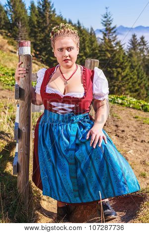 Portrait of a young chubby milkmaid in the mountains with festive costume