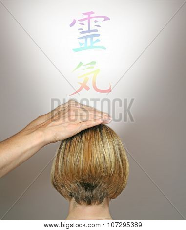 Female healer channeling healing energy through female client's chakra with a faint  rainbow colored Reiki Kanji symbol floating above on a neutral background poster