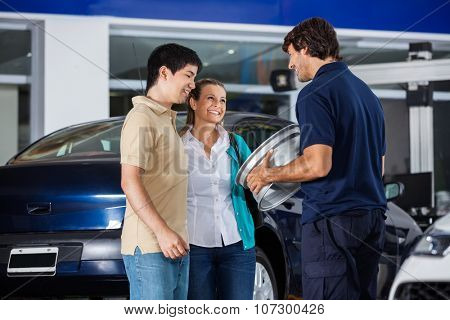 Happy male technician showing metallic hubcap to couple at garage