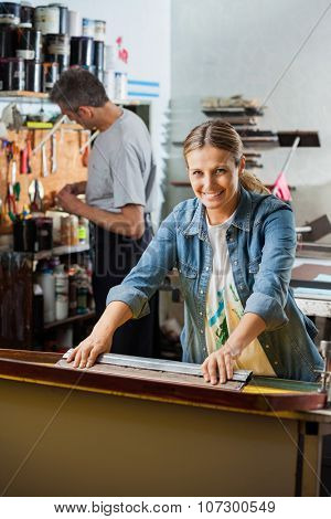 Portrait of confident female worker using squeegee while male colleague working in background at factory