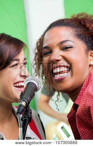 Portrait of excited singer with colleague performing in recording studio poster